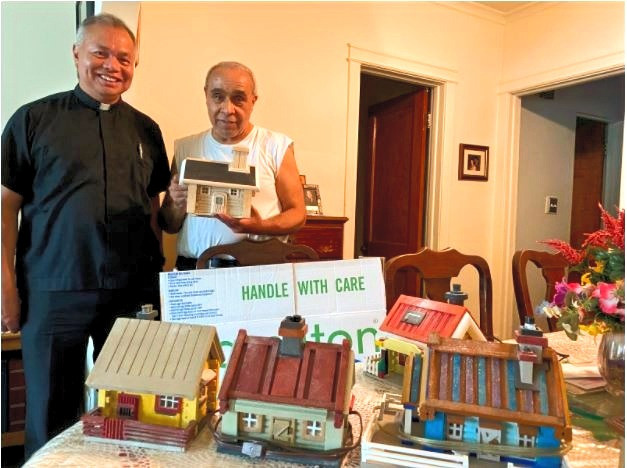 Orlando F., with Fr. Rene, Hospice Chaplain, showing some of his miniature houses.