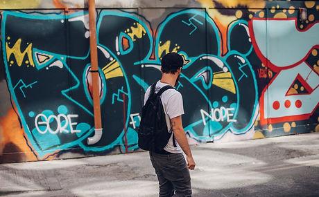 Man Looking at Colorful Graffiti Wall