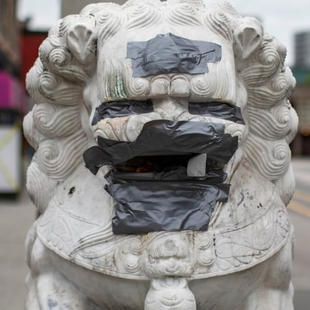 Graffiti is covered up by duct tape on the lions at the Millennium Gate in Chinatownon Wednesday. (Ben Nelms/CBC)