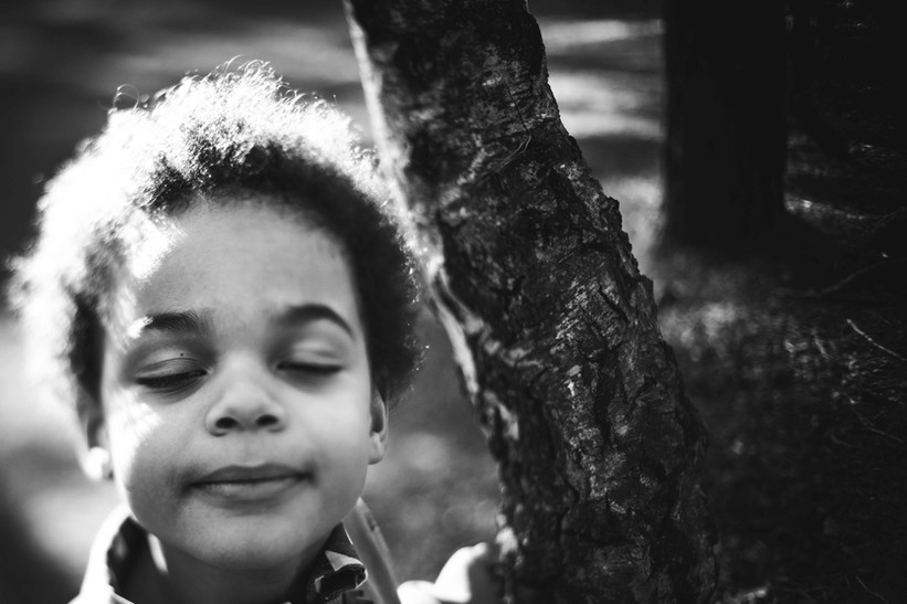 Black and white freelenssed image in a park of a young boy