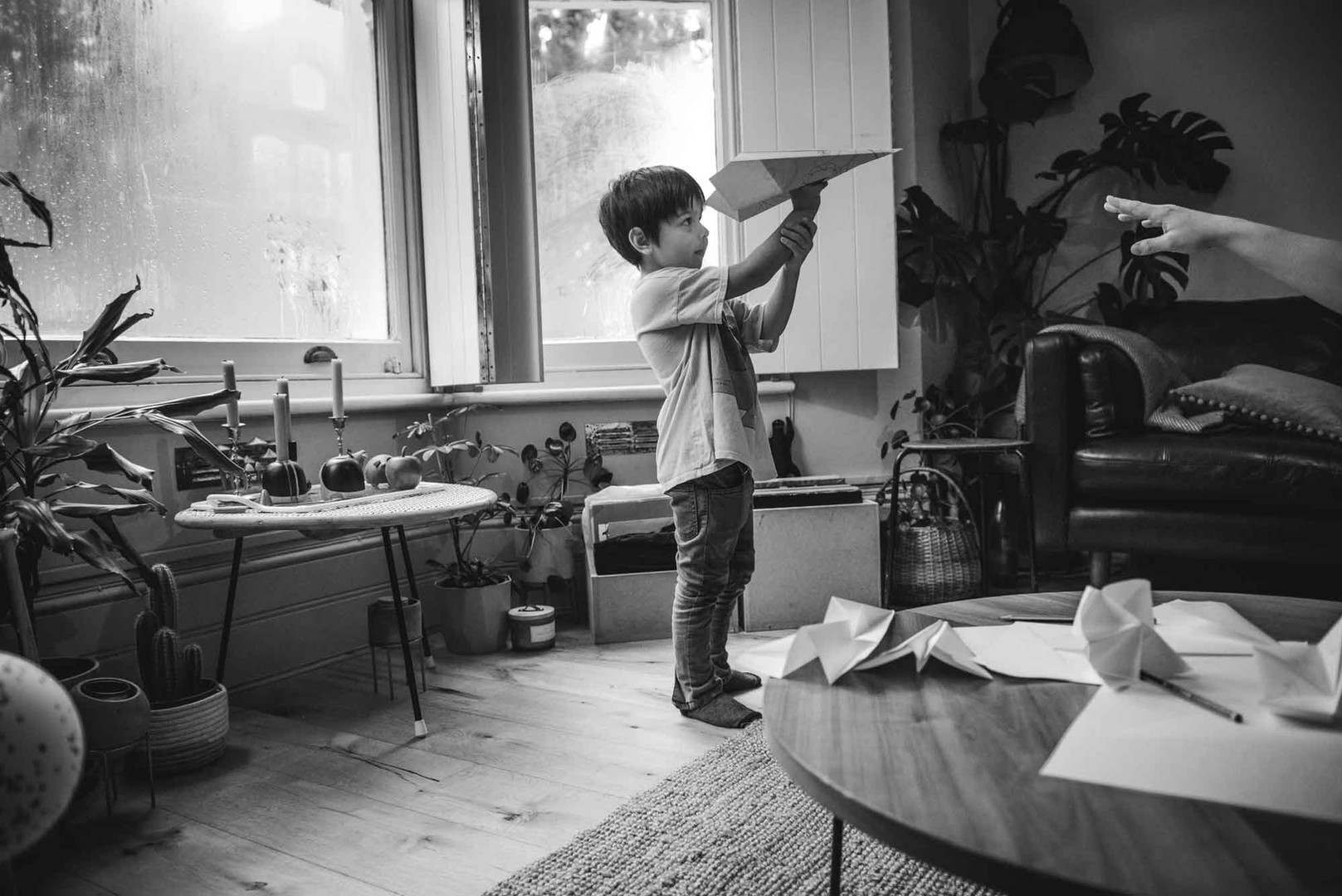 Boy playing with paper aeroplane. Family documentary photo