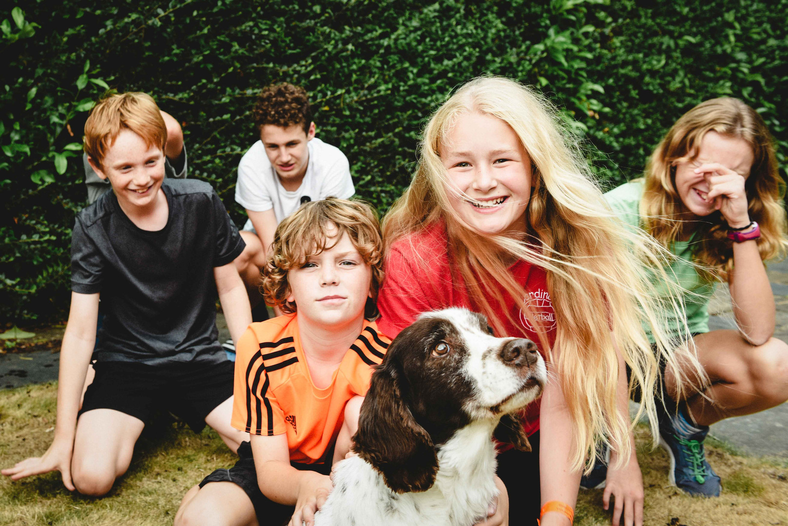 Children smiling together with family dog