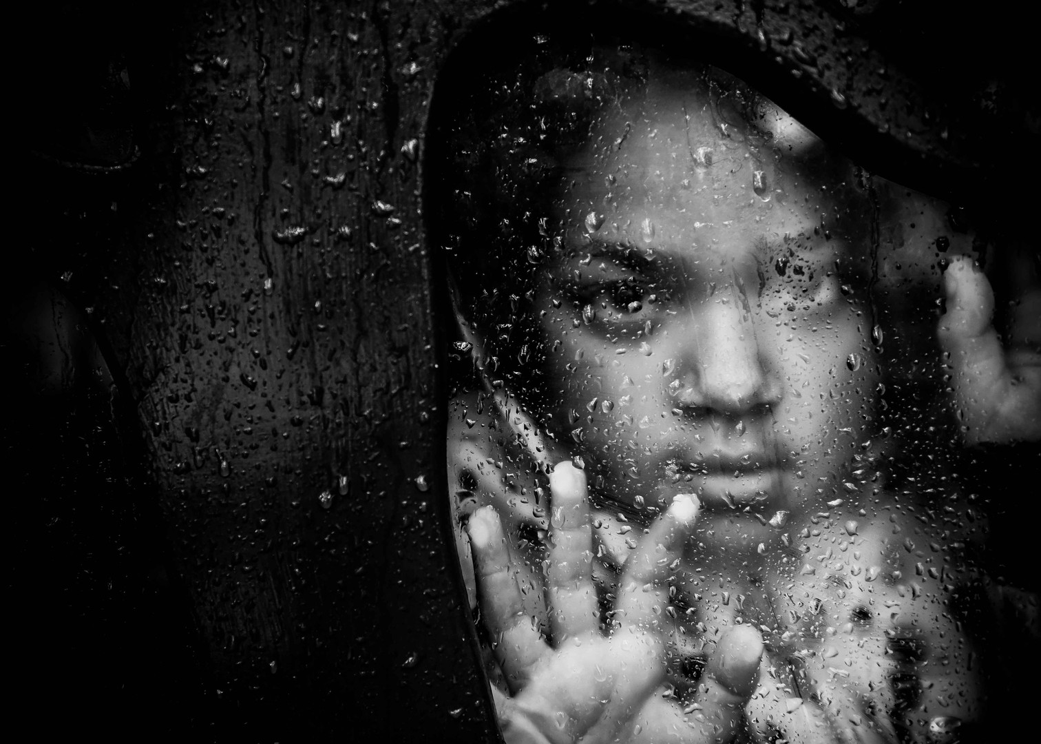 Black and white portrait taken through a glass window in the rain. Published in Shots Mag