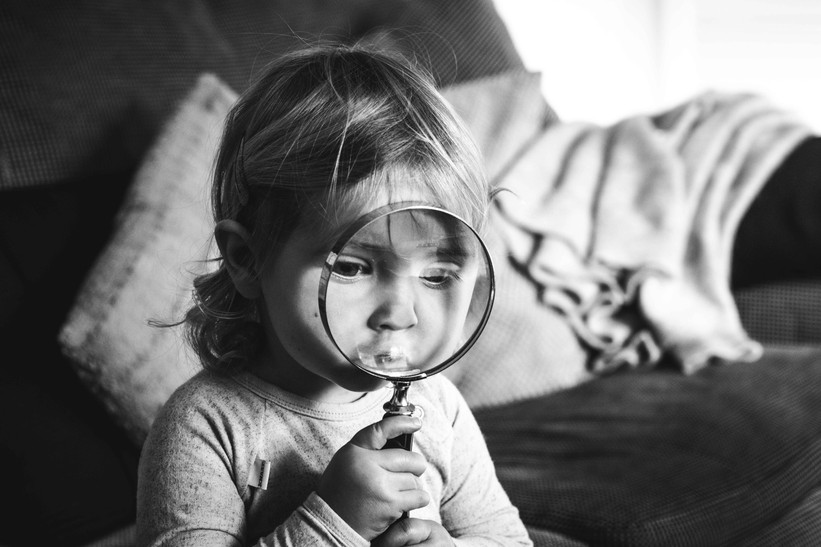 Black and white picture of youg girl holding a magnifying glass.