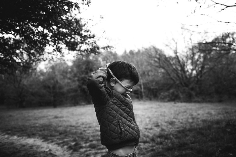 Black and white image of a boy in a park