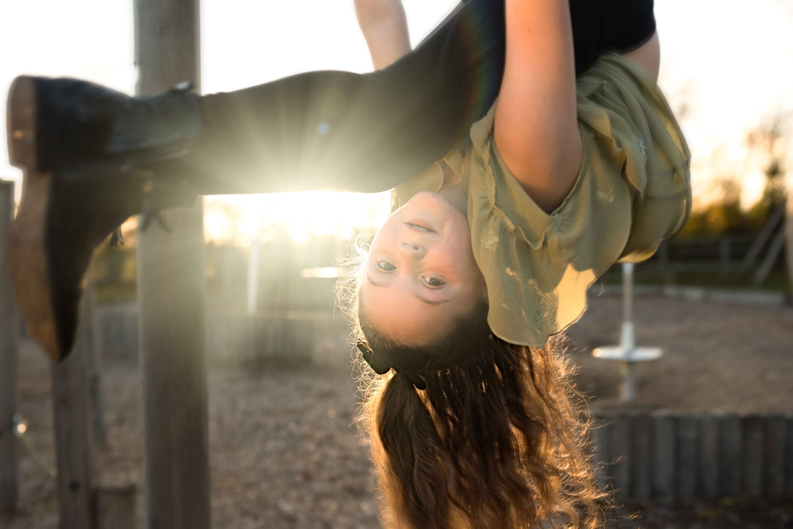 Girl hanging upside on bars in the park