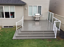 Gray composite deck with white railing and glass privacy wall