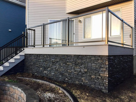 Deck with stone skirting and glass raililng