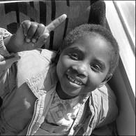 Il fait chaud ce jour-là. Le car scolaire va chercher les enfants du Centre à l'école d'Yvoir où une classe a été ouverte pour eux. Le car est plein. Les enfants sont joyeux. Les mamans les attendent à l'arrêt. Les goûters sont prêts...  Centre de la Croix-Rouge, Yvoir, 1995
