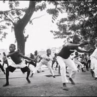 Ils viennent de la rue ou de familles aisées : une soixantaine de jeunes se retrouvent sur la place commerciale de Limete pour leur entraînement à la Capoeïra. Cet art martial, introduit en RDC au début des années 2000 par Braz, travailleur social de rue, de Dynamo AMO, est, entre autres, utilisé pour aider à la réinsertion des enfants dits «soldats». (République Démocratique du Congo, Kinshasa, 2016)