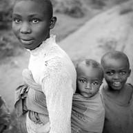 Banlieue de Kigali, le 13 avril 2004.  Petite mère, grande sœur. Le bébé porté sur le corps ne pleure pas. Il se balance au rythme de l'enfant qui le porte. De nombreux parents ont été tués au cours du génocide, sont morts du SIDA ou sont emprisonnés pour des crimes liés au génocide. Les enfants prennent souvent la responsabilité du foyer et de leurs cadets.