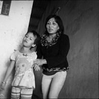 Maolen a 7 ans. Hué, la travailleuse sociale, est venue la chercher dans sa famille où elle avait passé un congé. Elle la ramène à la «Familly 5 » le centre d'hébergement où elle vit, sa famille ne pouvant s'occuper d'elle. (Vietnam, Danang, 2017)
