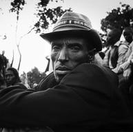 """Bisesero, le 18 avril 2004.  Dans le public, il y a les hommes qui ont résisté d'avril à fin juin 1994 aux miliciens et aux soldats hutus. Ils étaient 50.000 il n'en est resté que 800. """"Entre buissons et forêts / Sur la colline de Muyira / Reste une poignée d'hommes / Une poignée d'hommes / Qui maintenant meurent de chagrin"""". La cantate de Bisesero raconte leur histoire."""
