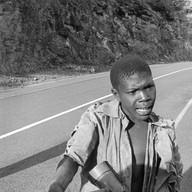 Sur la route entre Kigali et Kibuyé, le 17 avril 2004.  Il s'accompagne d'un instrument qui fait vaguement penser à un violon et qu'il a fabriqué lui-même. Son chant est lancinant et volontaire. Il nous regarde, il tend la main. Il aura gagné sa journée.