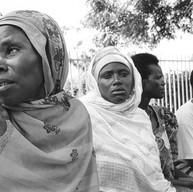 """Nyamata, le 16 avril 2004.  Les veuves du génocide tentent de s'organiser. Elles sont venues voir le spectacle du Groupov. Elles embrassent les acteurs. Elles parlent d'elles, de leurs maisons détruites, de leurs maris assassinés, des viols et du sida, et puis du retour des anciens génocidaires : """"Il revient chez lui après la prison. Il retrouve sa femme, ses enfants, sa maison. Nous, on meurt à petit feu à côté d'eux."""""""