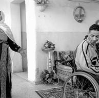 Camp d'Amari, le 7 décembre 2002  Ils vivent à treize dans la maison familiale. Un des fils a été tué par les Israéliens. Un autre, sourd et muet, a eu les deux jambes brisées pendant la première intifada. Il vit ici avec sa femme et son enfant. Le fauteuil roulant est bancal, il ne peut pratiquement plus se déplacer. Ils n'ont pas les moyens d'en acheter un autre.   Camp d'Amari, le 7 décembre 2002.  Ils vivent à 13 dans la maison familiale. Un des fils a été tué par les Israéliens. Un autre, sourd et muet, a eu les deux jambes brisées pendant la première intifada. Il vit ici avec sa femme et son enfant. Le fauteuil roulant est bancal, il ne peut pratiquement plus se déplacer. Ils n'ont pas les moyens d'en acheter un autre.