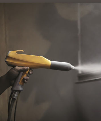 hand holding yellow spray gun