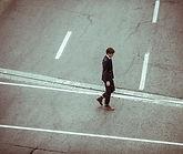 Mann läuft einsam über Straße
