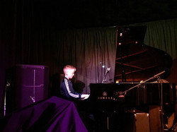 Student playing piano in performance