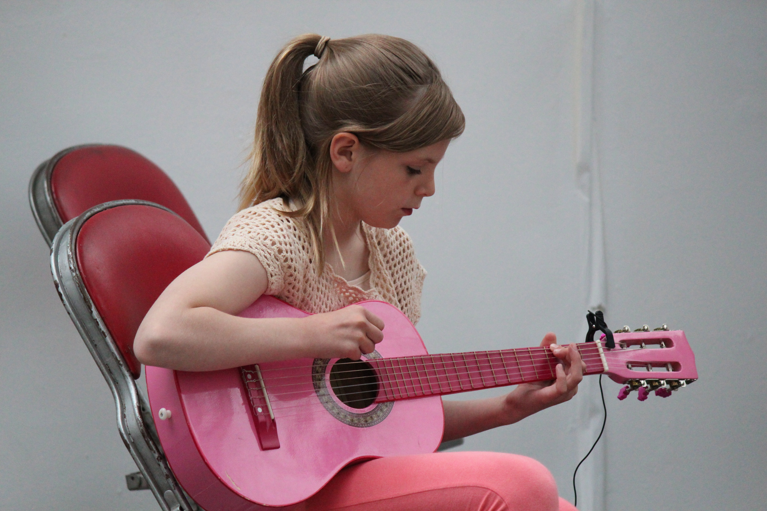 Young ESM student playing guitar