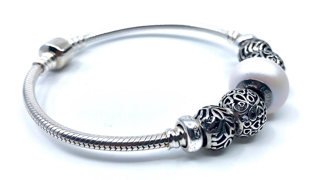 pulsera combina charms de plata con swarovski