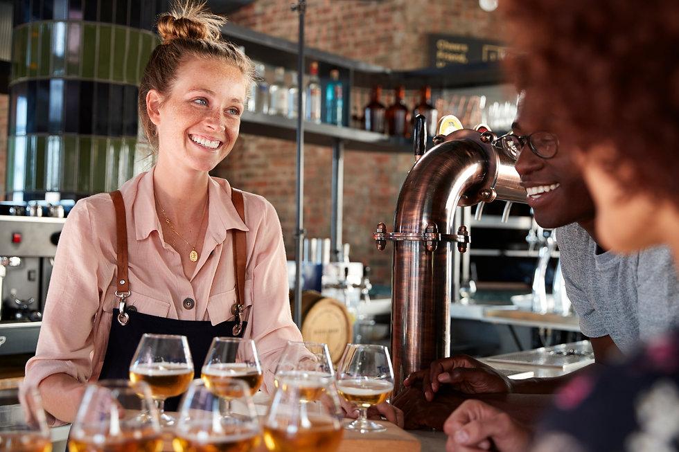waitress-serving-group-of-friends-beer-tasting-in--A63P2J8.jpg