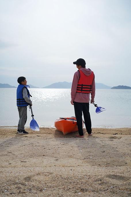 大串のビーチで海を目の前に会話をしている2人