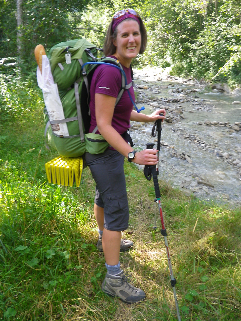 Happy female hiker on Tour du Mont Blanc stuffed her backpack with local food