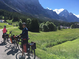 Two women on their toruig bikes in front of the Alps