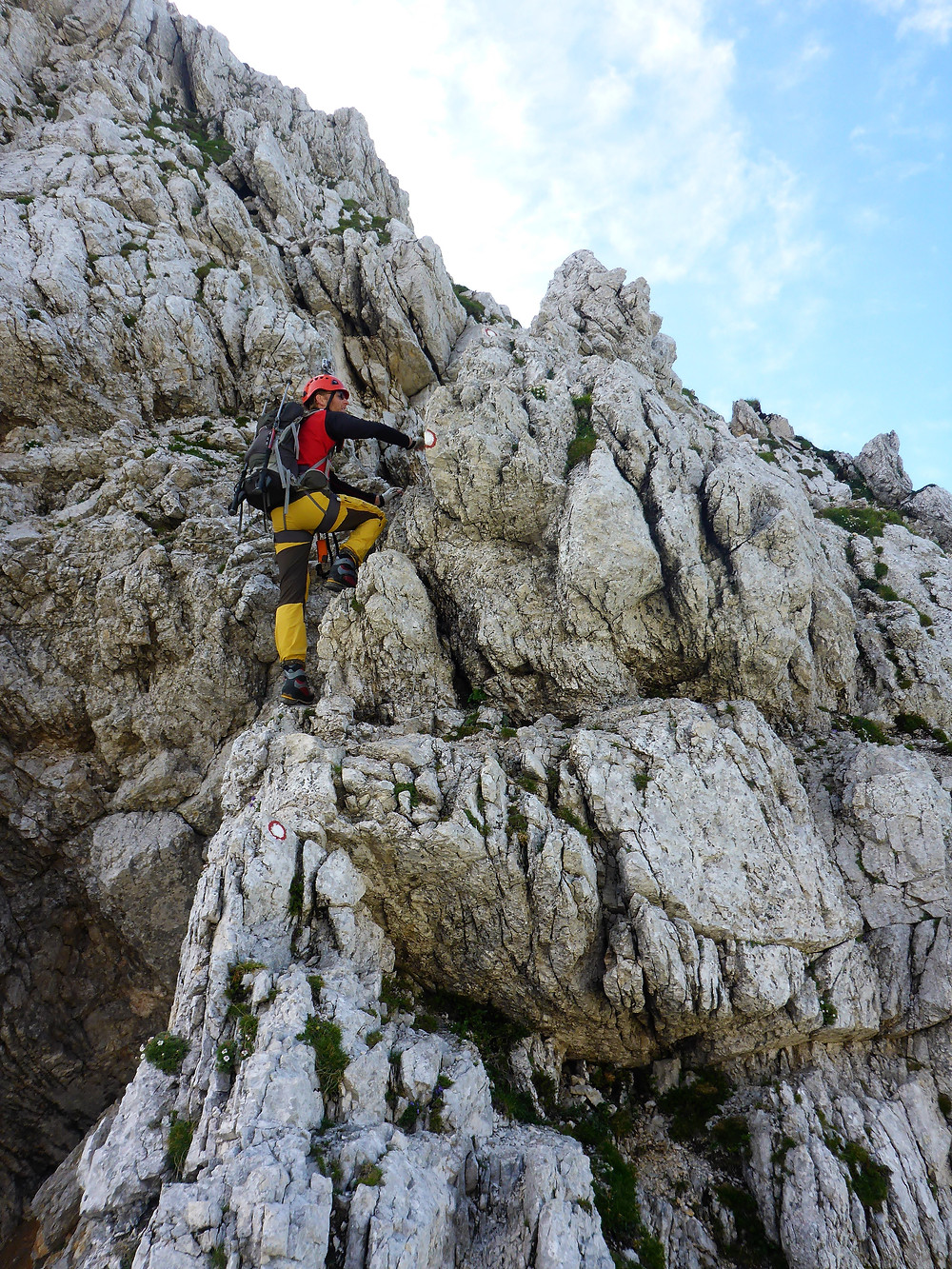 Make hiker climbing a face of rocks in Slovenia