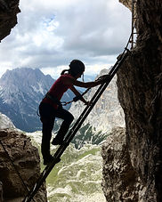 Women is climbing up a ladder on a Via Ferrata in the Dolomites