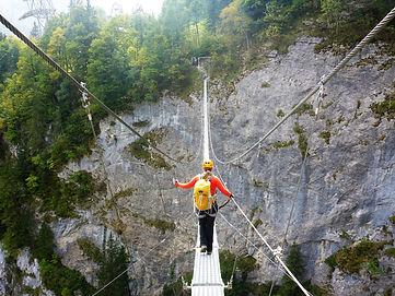 Climber on swing bridgein the Alps
