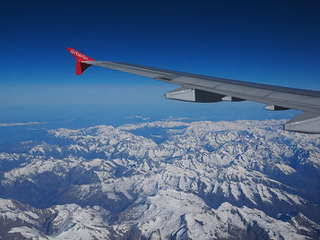 Aircraft wing above the Alps in winter