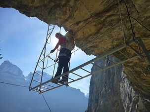 Person standing on a ladder on a Via Ferrata in the Dolomites