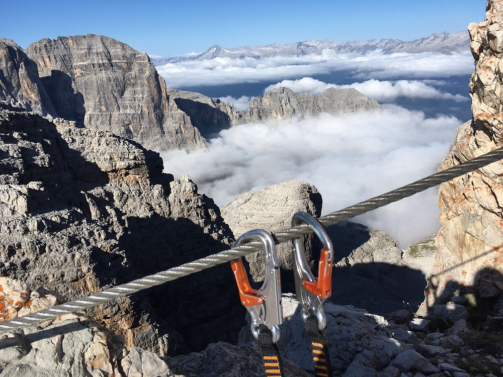 Steel cable and carabiners of a climber resting above the mountain peaks on a Via Ferrata through the Dolomites