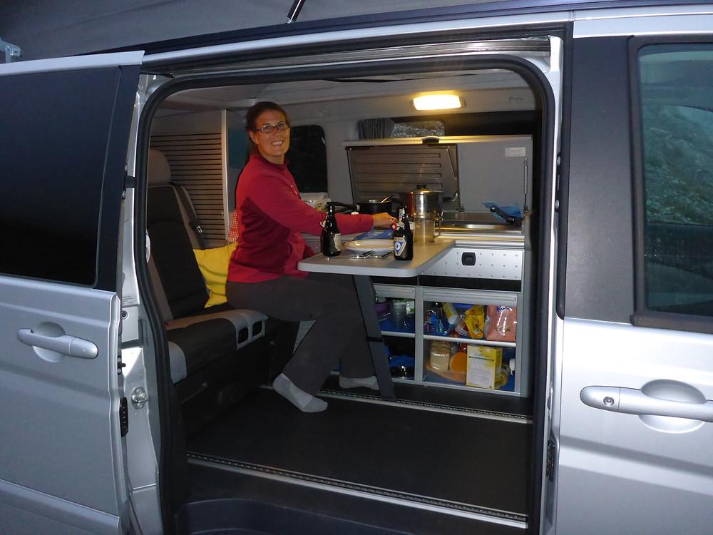 Female adventurer sitting inside of a camper van