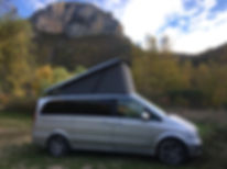 Campervan with fully raised roof in the Alps