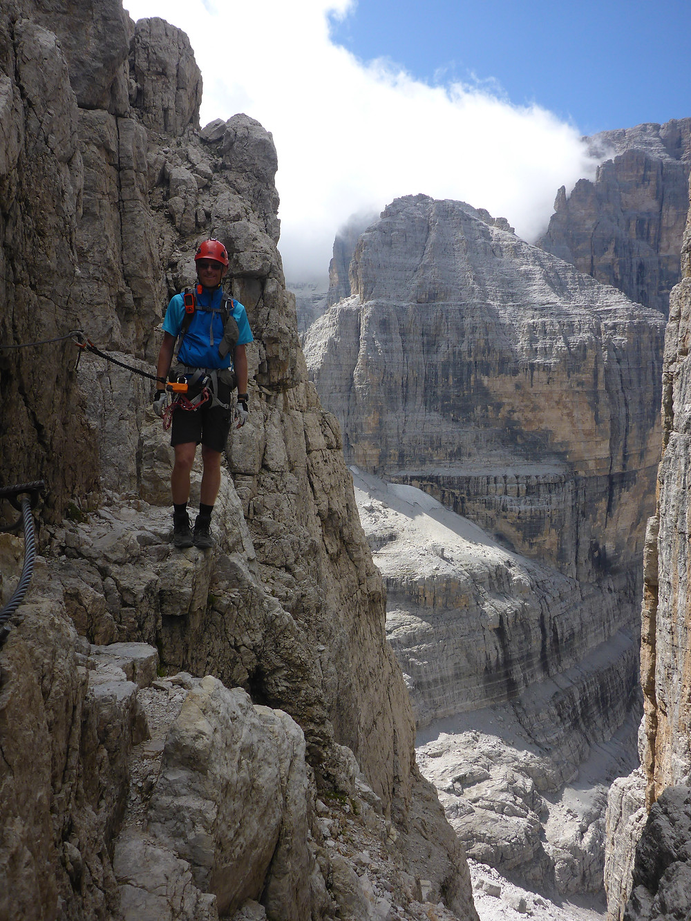 Male hiker close to an abyss on a Via Ferrata in the Dolomites