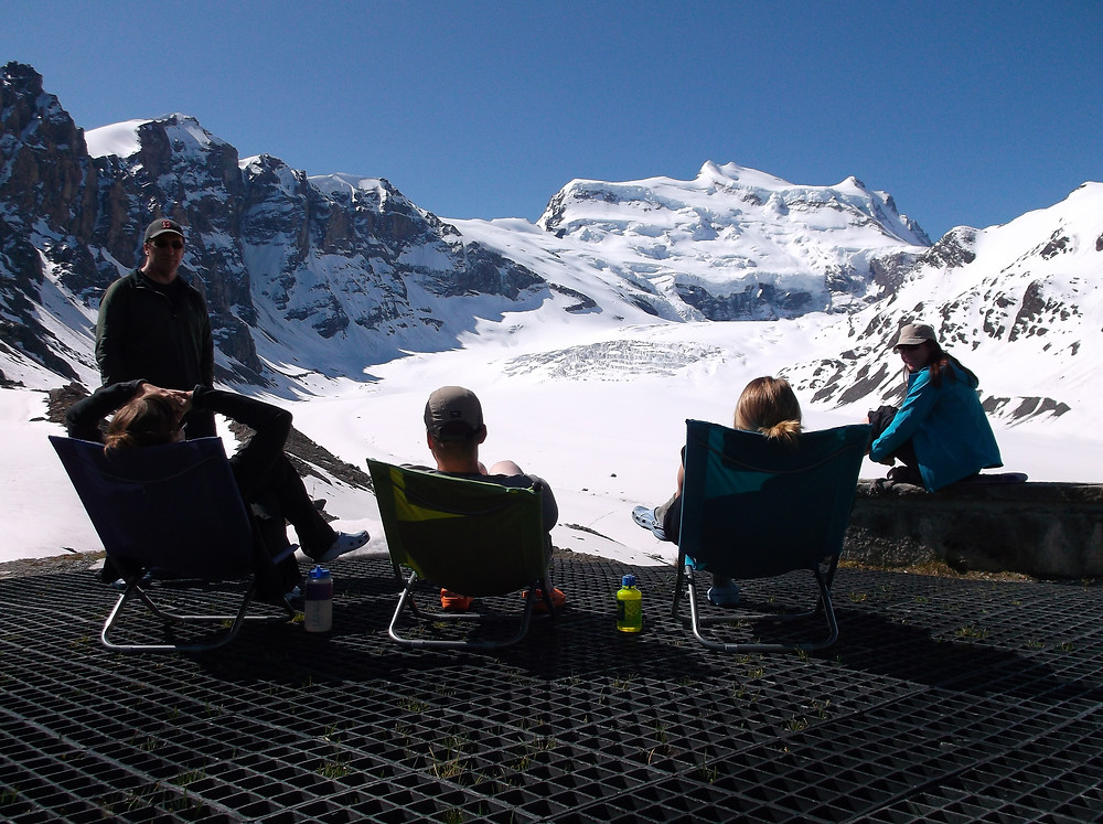 Group of people sitting in camping chairs and watching the snowy mountains