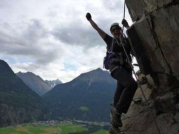 Climber holding on to a steel cable on a Via Ferrata