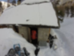 Person entering a mountain hut surrounded by snow