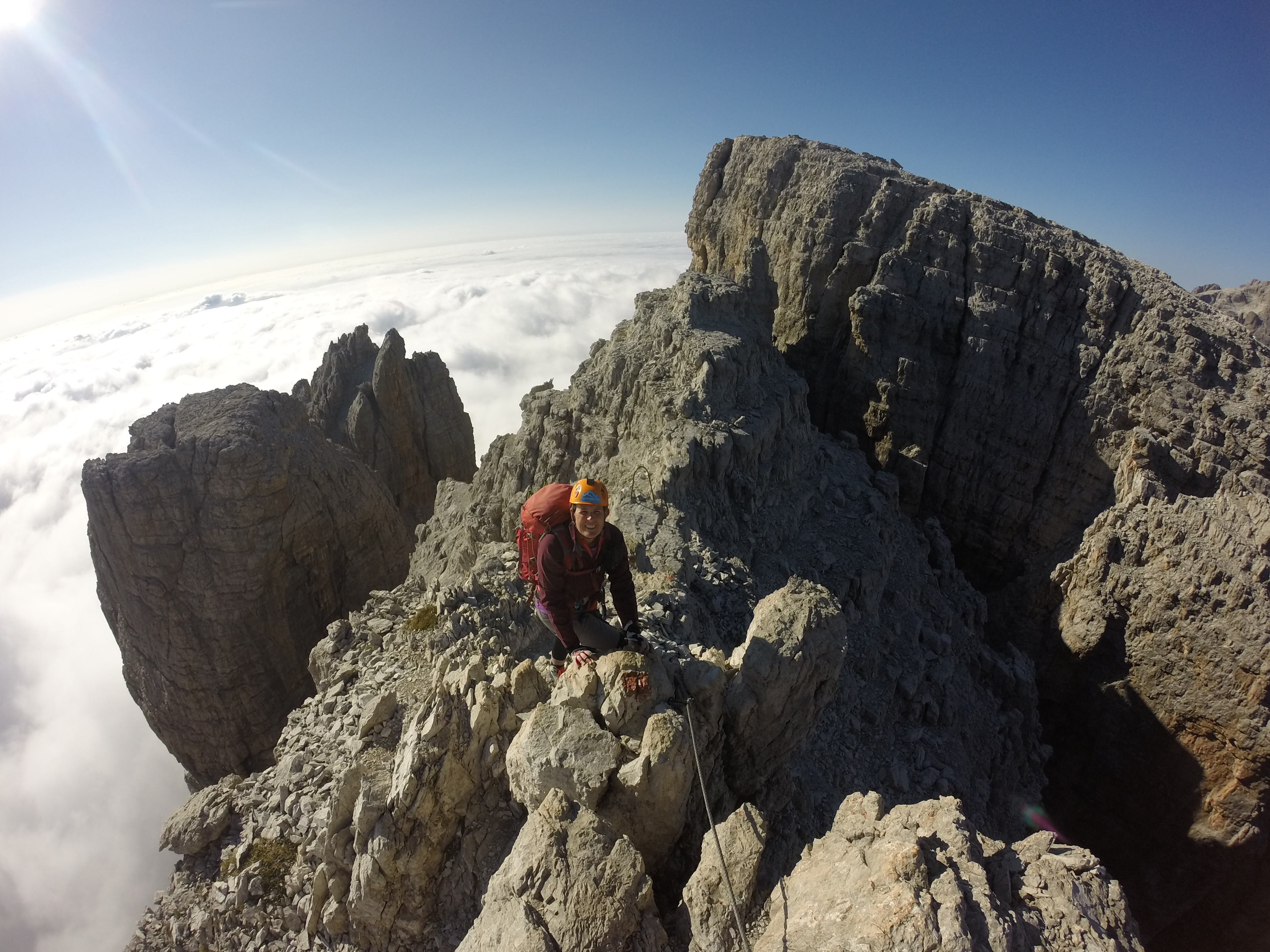 Climber above the clouds on a summit