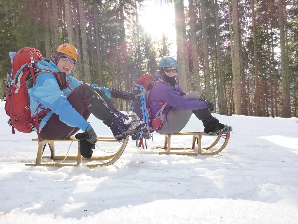 Two people on their sleds on a slope in the forest