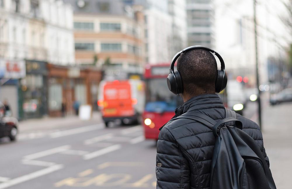 A man wearing earphones walks in the street