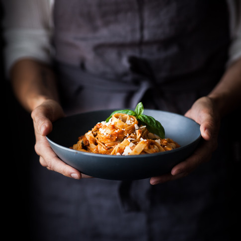 portrait of a person in a blue apron holding a bowl of pasta topped with basil.