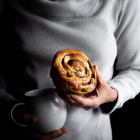 a portrait of a person wearing a grey sweater holding a cinnamon bun and a white coffee mug.