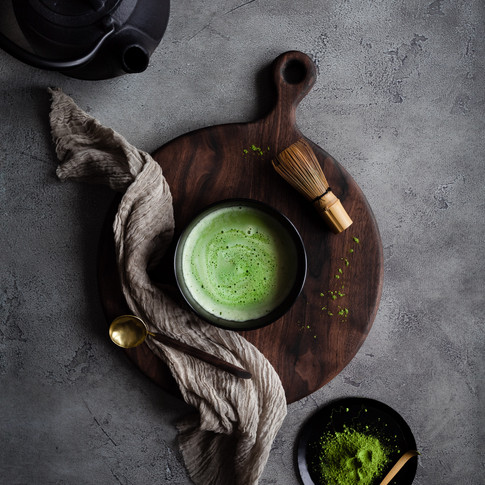 overhead portrait of a bowl of matcha tea on a wooden cutting board with a matcha wisk and a black tea pot.