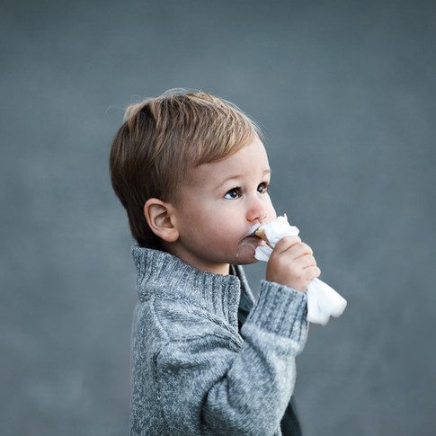 portrait of a small child wearing a grey sweater eating ice cream.