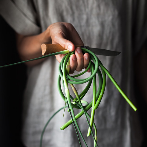 portrait of a person in a beige shirt holding a knife and fresh garlic scapes.