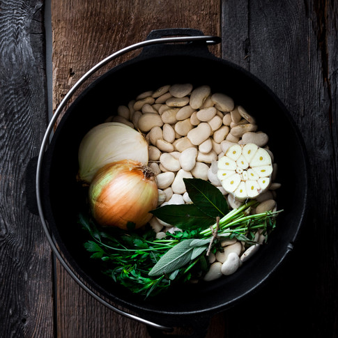 overhead image of a castiron pot on a wooden surface filled with dry beans, onion, herbs and garlic.
